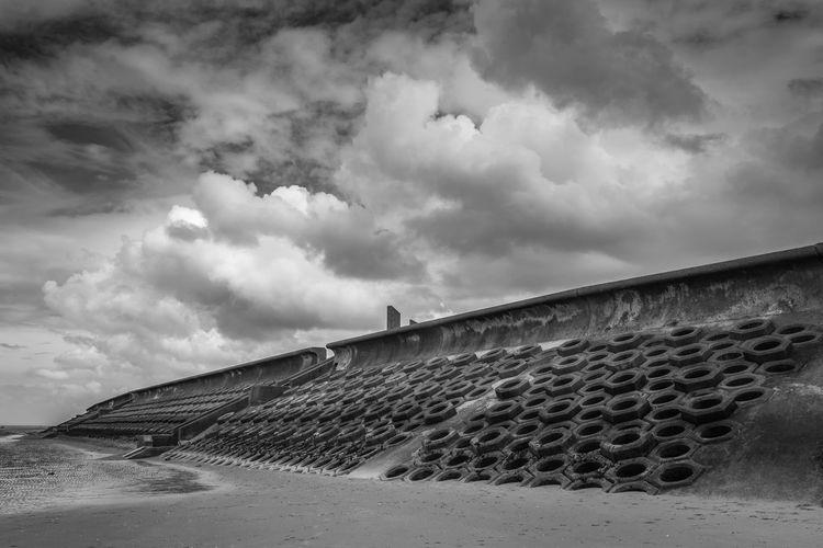 Groynes by wall at sandy beach against cloudy sky