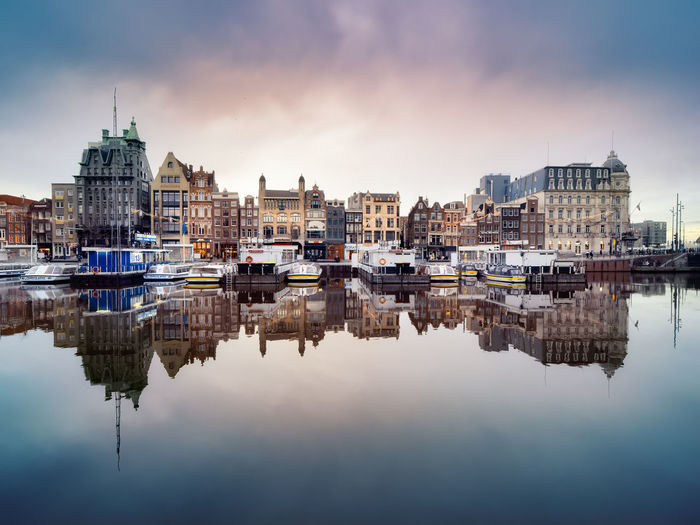 Reflection of historic canal houses and tourist canal boats in the damrak canal in amsterdam.