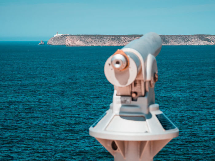 Coin-operated binoculars by sea against clear sky