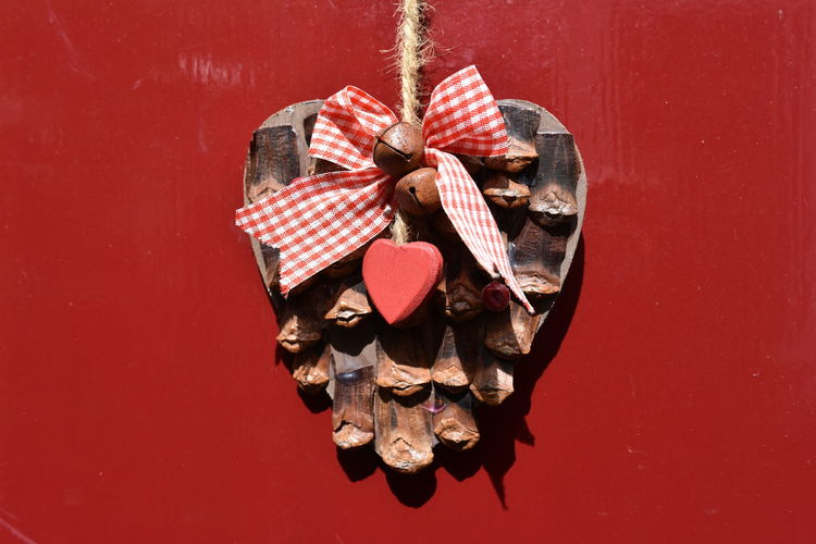 Close-up of pine cone with heart shape hanging on wall