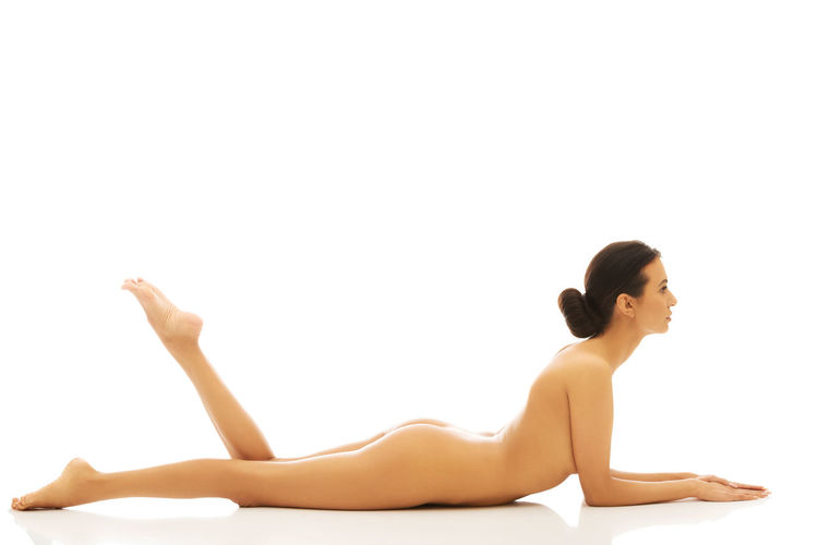 Naked woman lying against white background
