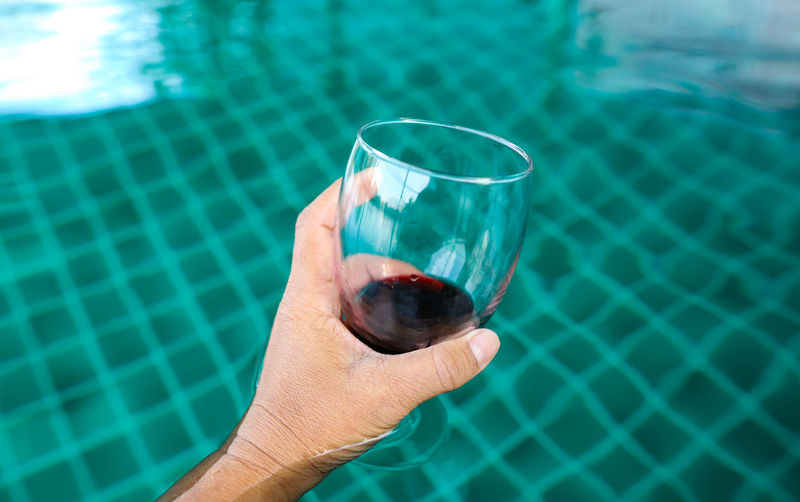 Midsection of man drinking water in swimming pool