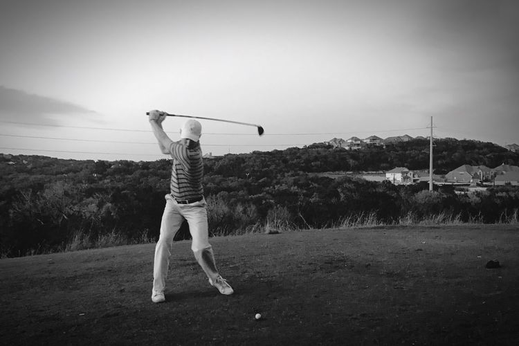 Full length of man playing golf on field against sky