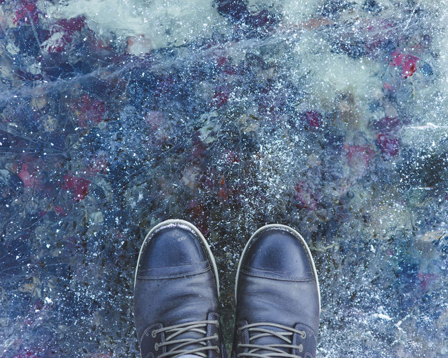Close-up of shoes on frozen lake