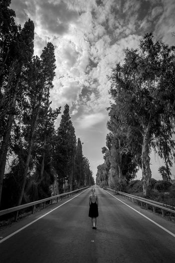 Full Length Rear View Of Woman Standing On Empty Road Amidst Trees Against Sky