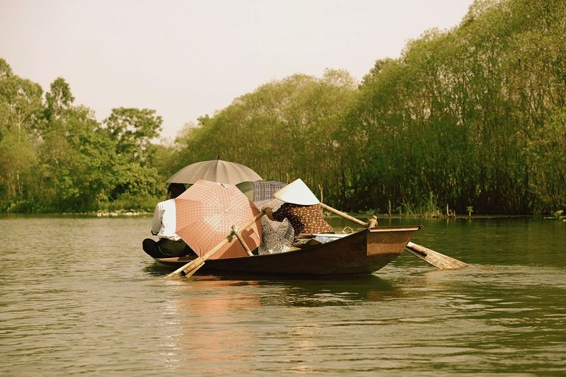 People with umbrellas on boat in mekong river against sky