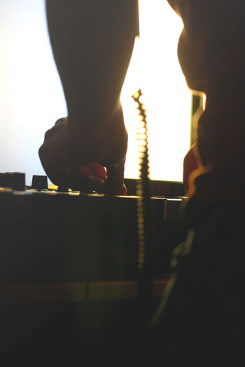 Midsection of dj adjusting sound mixer