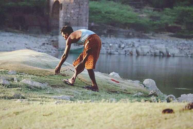 Full Length Of Fisherman Working On Net