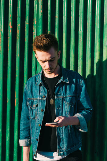 Young man using phone while standing against metal wall