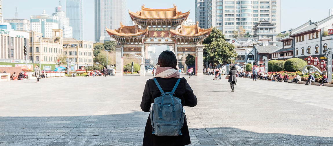 Rear view of woman standing against temple