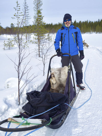 man leaning on sled against cloudy sky in forest during winter Winter Animal Mammal Real People Animal Themes Snow Domestic Animals One Animal One Person Cold Temperature Leisure Activity Pets Domestic Warm Clothing Dog Nature Canine Vertebrate Lifestyles Outdoors Pet Owner