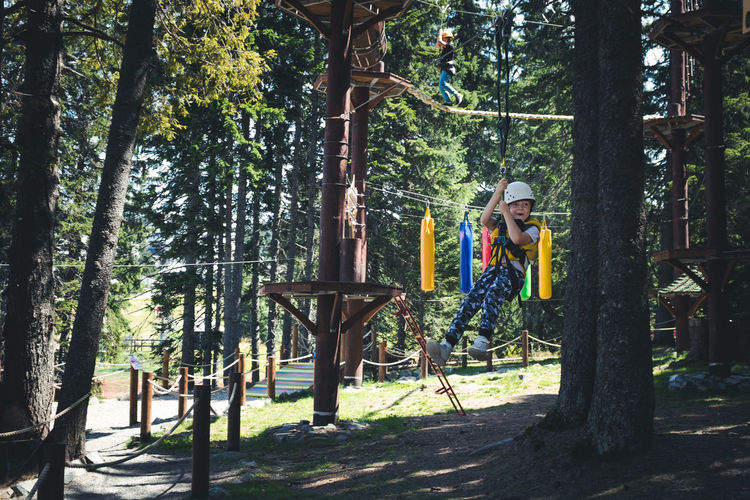 Happy boy having fun while rappelling from zip line in adventure park.