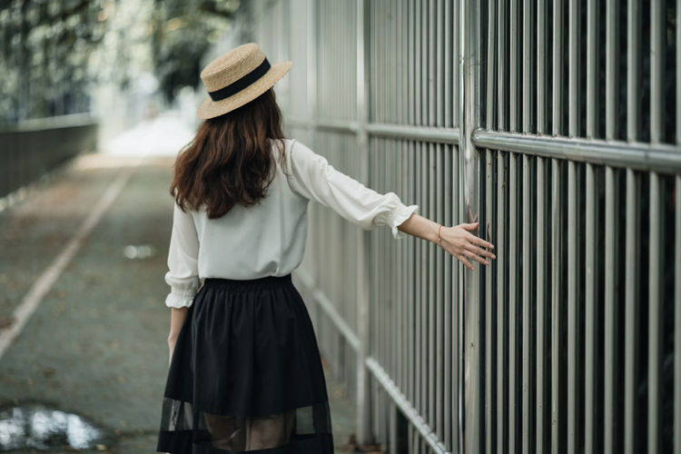 Rear view of woman standing against railing