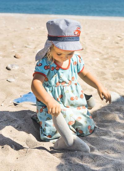 Full length of cute boy sitting on sand at beach