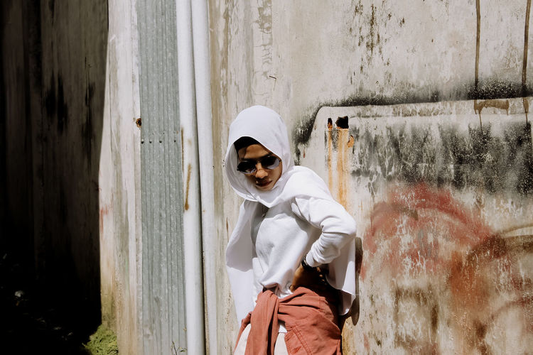 Portrait of girl wearing sunglasses standing against wall
