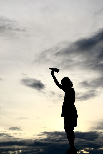 Silhouette girl holding paper airplane against sky