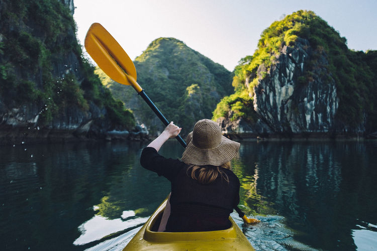 Rear View Of Woman Kayaking In Lake Against Mountain
