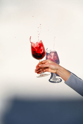 Hand holding red wine against white background