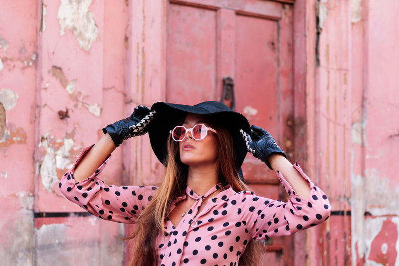 Close-up portrait of model in pink dress and gloves holding black hat in london