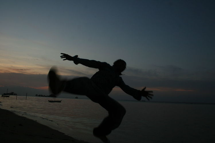 Silhouette Of Man Jumping At Sea