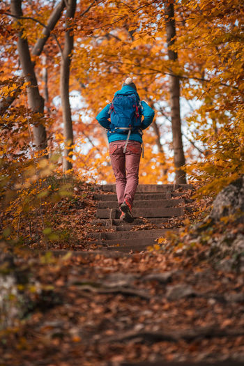 Rear view of woman walking on footpath during autumn