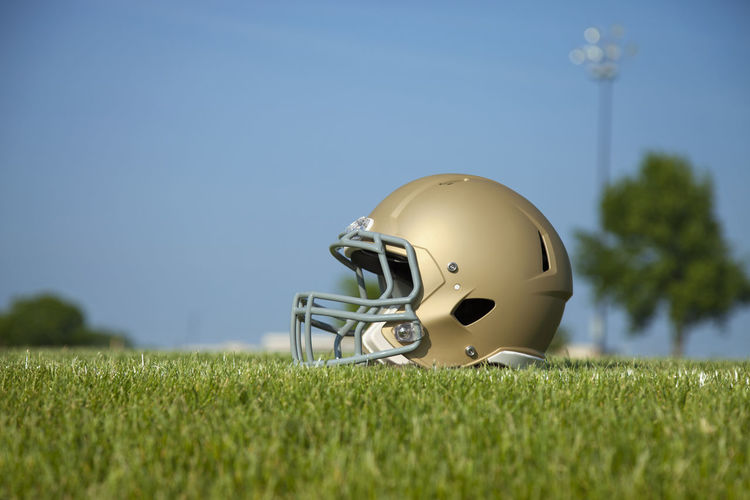 Low angle selective focus view of gold football helmet on grass field Football Helmet Low Angle Field Grass Selective Focus Sunlight Blue Sky Light Tree Facemask Sports American Gold Protective Safety Headgear Equipment Color Image Photography No People Copy Space
