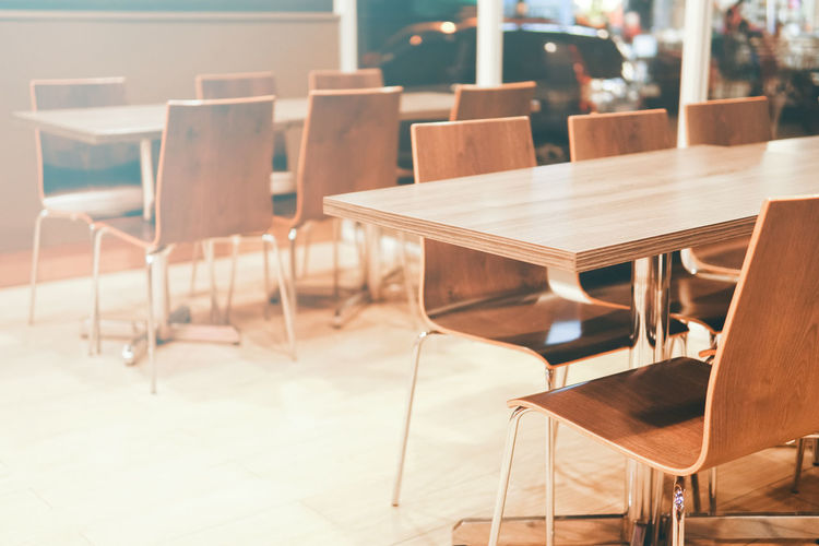 Copy-space image of moody empty restaurant with nice blurry effect background Absence Arrangement Brown Business Cafe Chair Empty Flooring Focus On Foreground Food And Drink Furniture In A Row Indoors  Luxury No People Relaxation Restaurant Seat Selective Focus Table Wood - Material