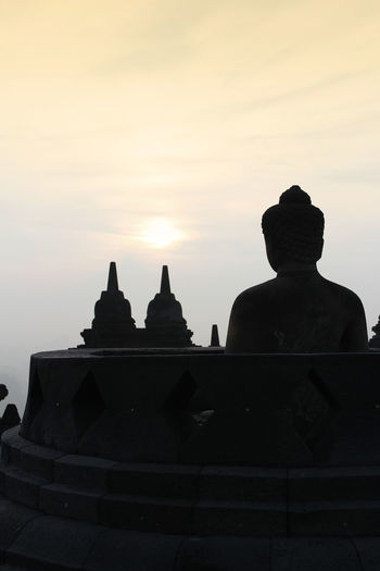Silhouette Borobudur Temple with the Buddha statue during sunrise, Yogyakarta, Indonesia Borobudur Temple Yogyakarta Ancient Civilization Architecture Belief Buddhism Building Built Structure Dawn History Nature No People Place Of Worship Religion Sculpture Silhouette Sky Spirituality Sunrise The Past Tourism Travel Travel Destinations