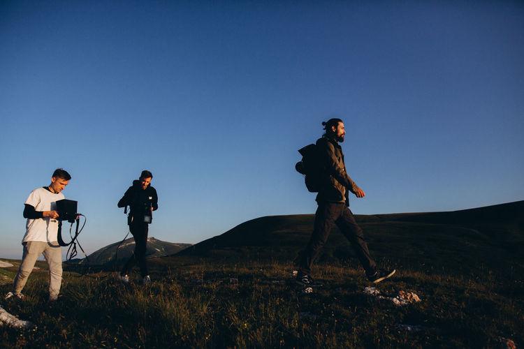 People walking on field against clear sky