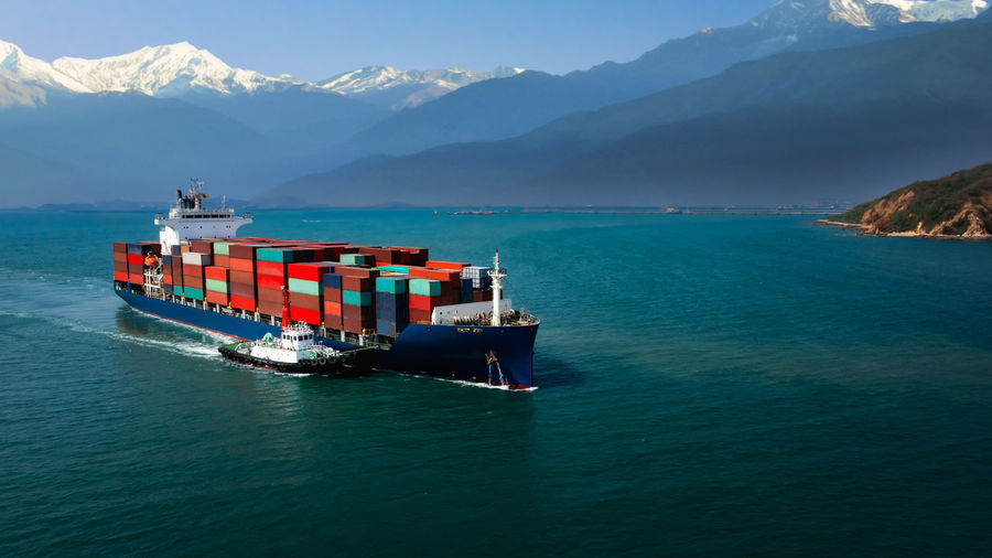 Aerial view container cargo ship and tugboat floating carrying commercial container in import export