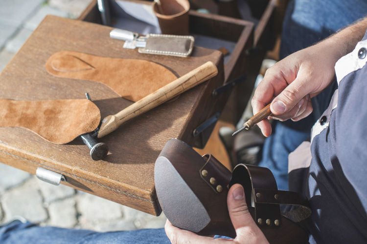 Shoes Shoemaker Craft Leather Hands Handmade Work Tools One Person Human Hand Real People Hand Human Body Part Holding Working Work Tool Skill  Occupation Tool Hand Tool Workshop Men Art And Craft High Angle View Wood - Material Indoors  Workbench Finger