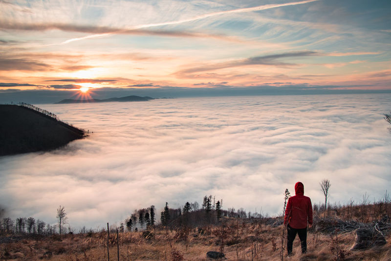 Man aged 20-25 and a red jacket stands on slopes of mount ondrejnik and looks at sunset on radhost