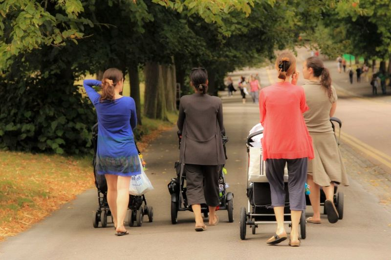 Rear View Of Women With Baby Carriages On Street