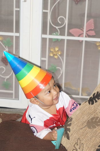Smiling boy wearing party hat at home