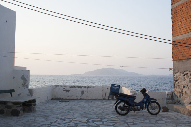 Bicycle by sea against sky in city