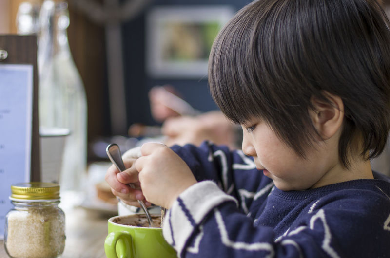 Side view of boy having breakfast at home