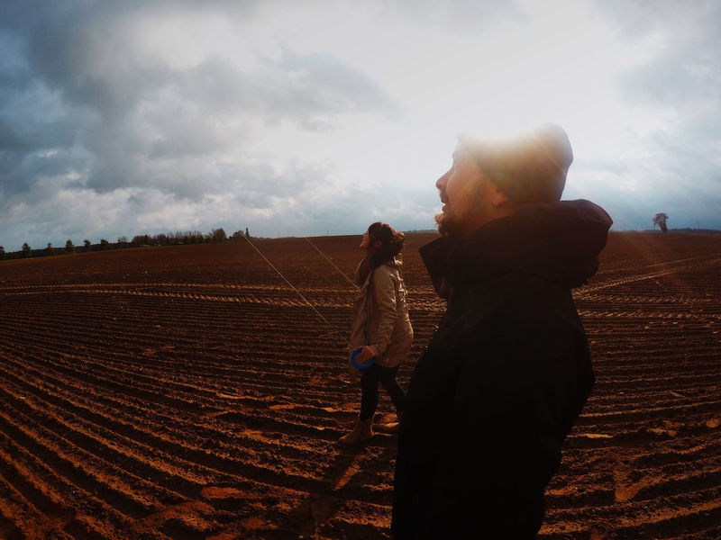 Agriculture Beauty In Nature Bonding Casual Clothing Cloud - Sky Day Field Friendship Full Length Landscape Leisure Activity Lifestyles Love Men Nature Outdoors Real People Rear View Sky Standing Togetherness Two People Women Young Adult Young Women