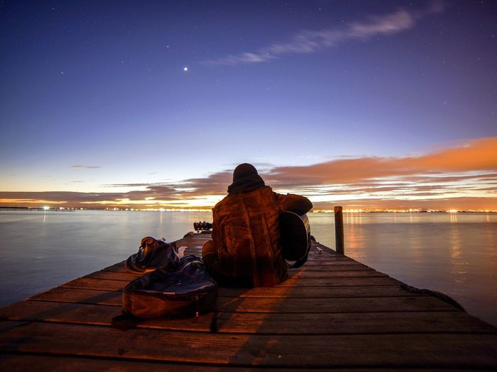 Rear View Of Man Playing Guitar While Sitting On Jetty Over Lake Against Sky At Dusk