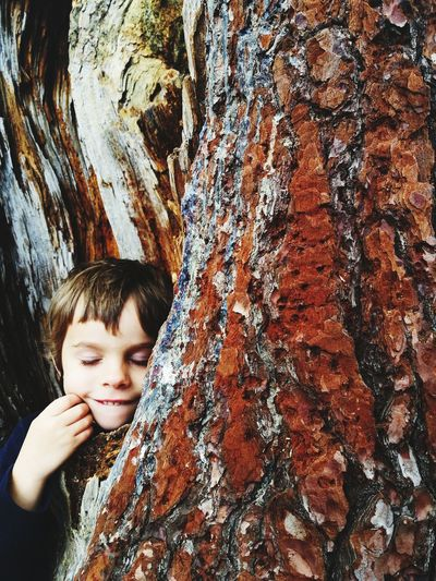 Cute Boy Leaning On Tree Trunk