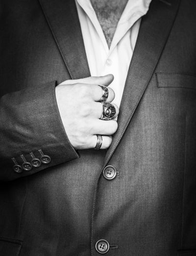 Close-up midsection of man wearing blazer and rings
