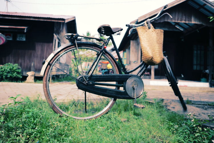 Bicycle parked outside house on field