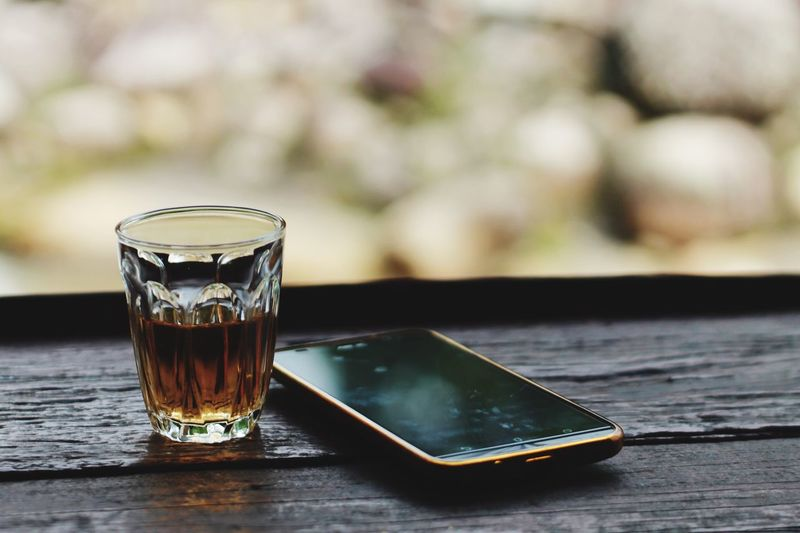 Close-up of drink and smart phone on wooden table