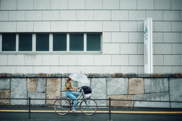 Man sitting on wall of building