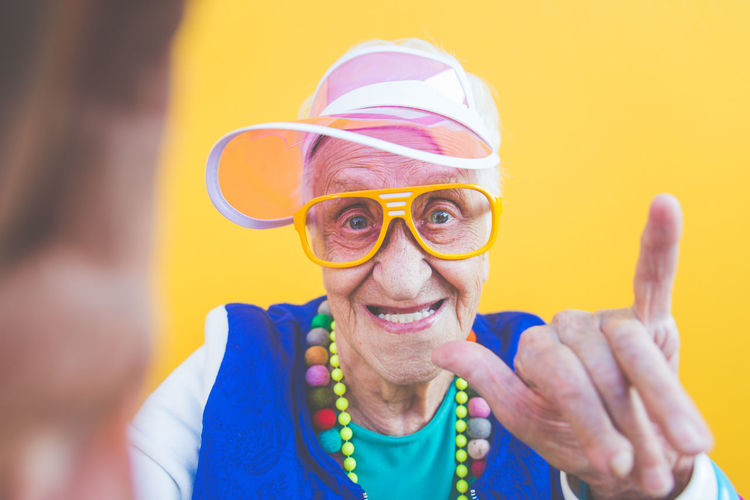 Portrait of senior woman wearing colorful jewelry standing against yellow background