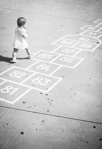 High angle view of girl playing on footpath