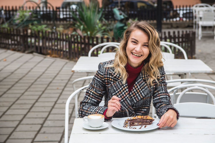 Portrait of happy young woman having dessert with coffee at outdoor cafe