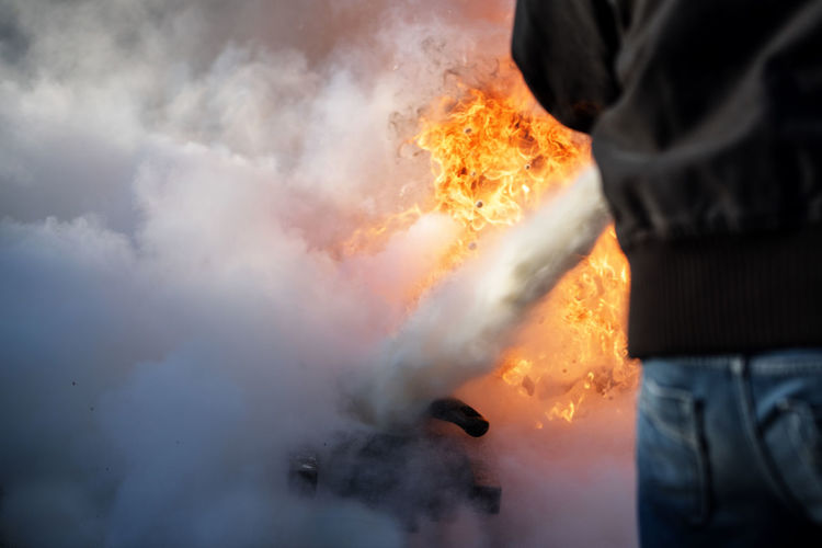 man from behind is fighting a fire with foam from a fire extinguisher, copy space in the smoke Burning Accidents And Disasters Behind Burning Danger Extinguisher Fighting Fire Fire - Natural Phenomenon Firefighter Flame Foam Heat Heat - Temperature Human Body Part Inferno One Person Outdoors People RISK Safety Smoke - Physical Structure Spraying