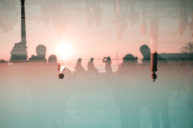 Double exposure image of people against sea and sky