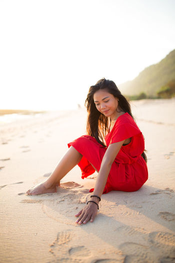 Portrait of happy woman sitting on beach against clear sky