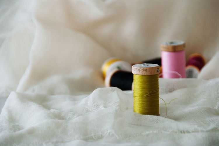 Spool Of Colorful Threads On White Fabric